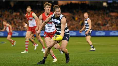 Mitch Duncan of the Cats is shadowed by Luke Parker of the Swans.