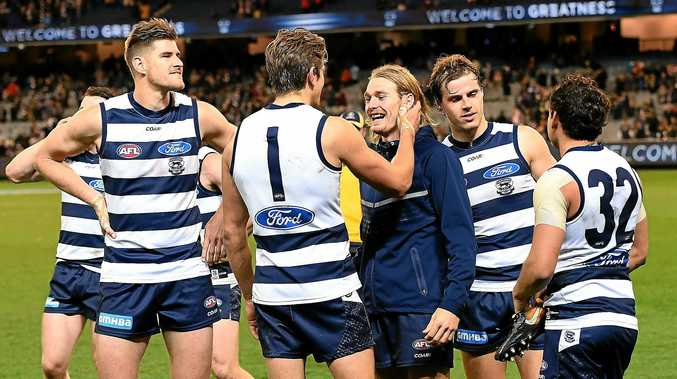 Cats players celebrate after their win over the Swans.