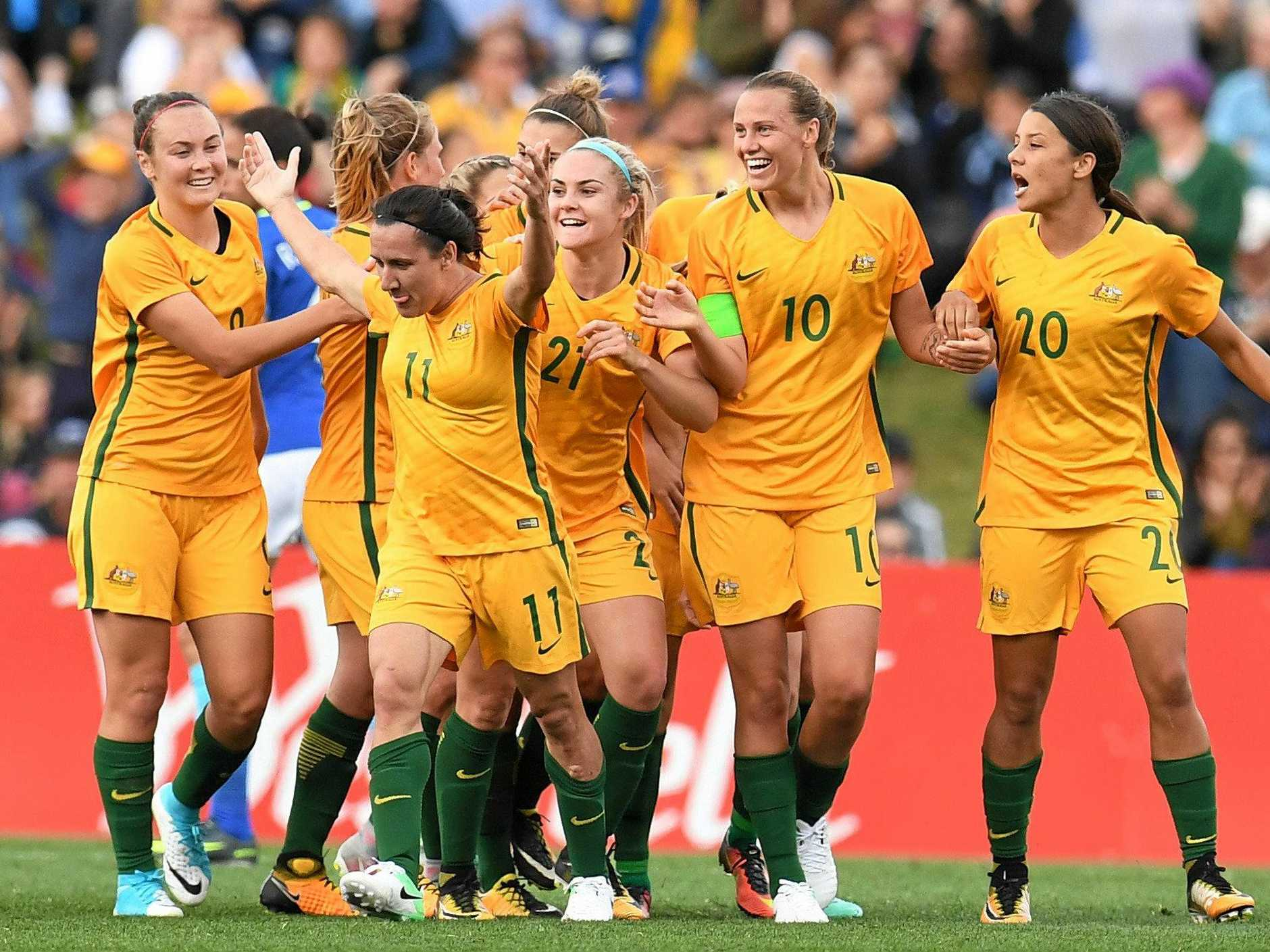 Lisa De Vanna of Australia throws her arms in the air as she celebrates her opening goal against Brazil.