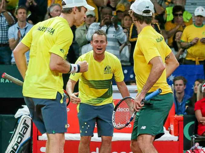 Australian team captain Lleyton Hewitt (centre) cheers on doubles players John Peers and Jordan Thompson  in Brussels