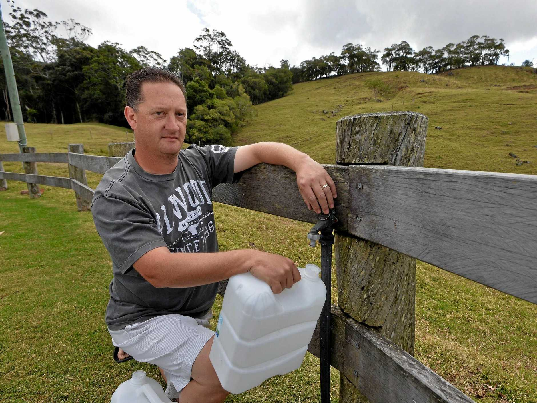 CRISIS POINT: John Brown, like most Bald Knob residents, is down to the dregs of his rainwater tank.