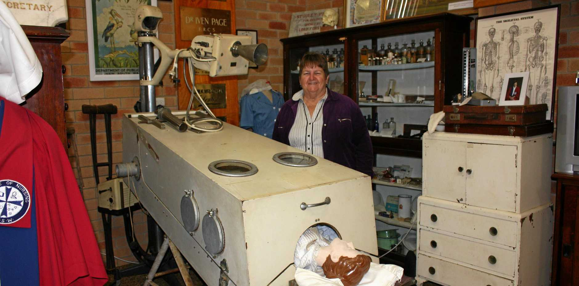 MIRACLE BOX: Schaeffer House volunteer Suzanne Gibson in the museum's medical section with the iron lung. The tall structure behind it is an X-ray machine.