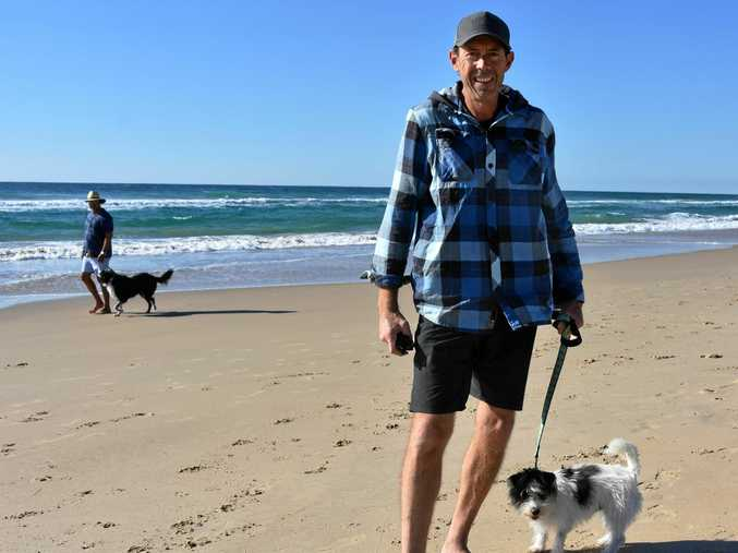 DOGGED ISSUE: Troy Dare and Sunny are happy with the dog beach access rules the way they are.