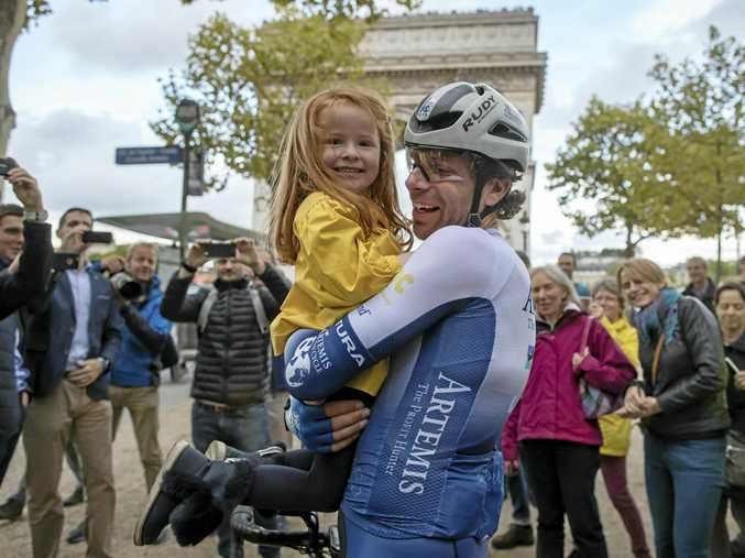 British athlete and adventurer Mark Beaumont holds his daughter as he arrives in Paris after cycling 29,000 kilometers around the world