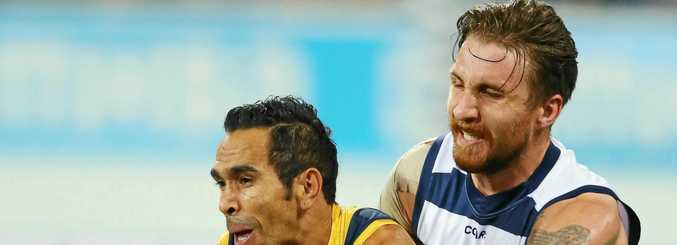 Zach Tuohy of the Cats (right) tackles Eddie Betts of the Crows.