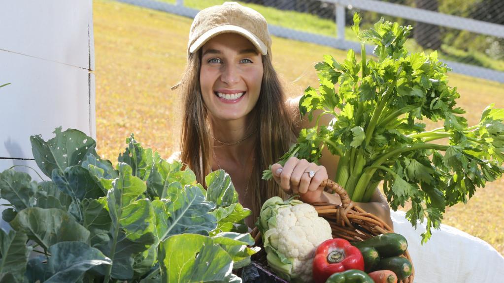 Vegan influencer Loni Jane with vegetables in her backyard veggie patch. Picture Glenn Hampson
