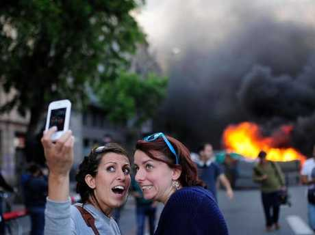 Girls pose in front of flames at May Day protests in Barcelona.