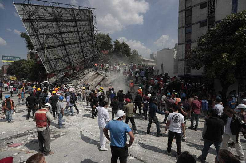 Rescue workers and volunteers search a building that collapsed after an earthquake in the Roma neighborhood of Mexico City, Tuesday, Sept. 19, 2017.