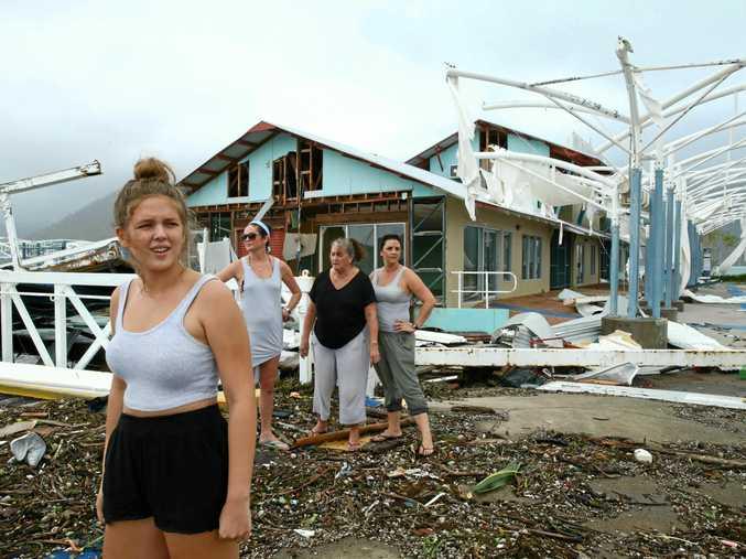 Airlie Beach residents Maika McDonald,15, Lauren Squires, Karen Gordon, and Katelin Gordon, survey the damage at Shute Harbour after cyclone Debbie. Photographer: Liam Kidston.