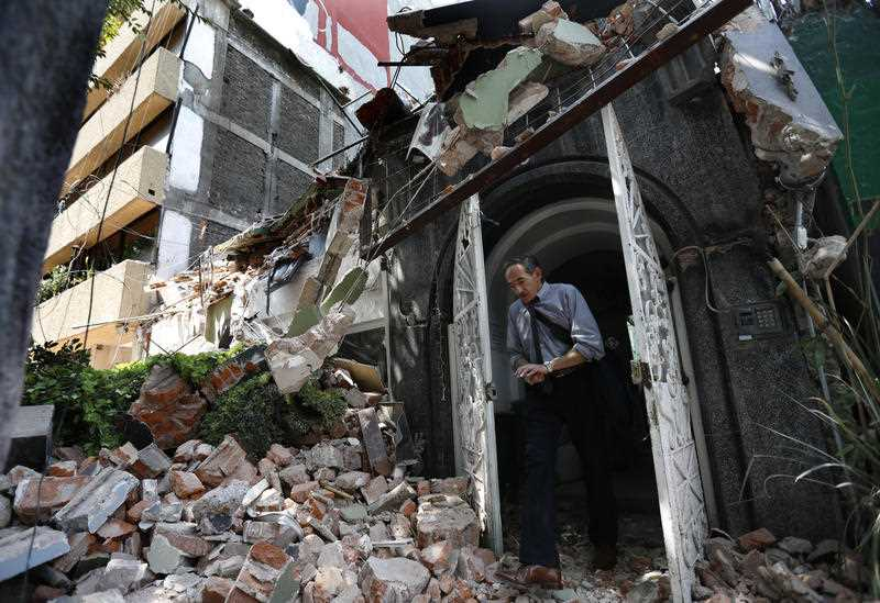 A man walks out of the door frame of a building that collapsed after an earthquake, in the Condesa neighborhood of Mexico City,