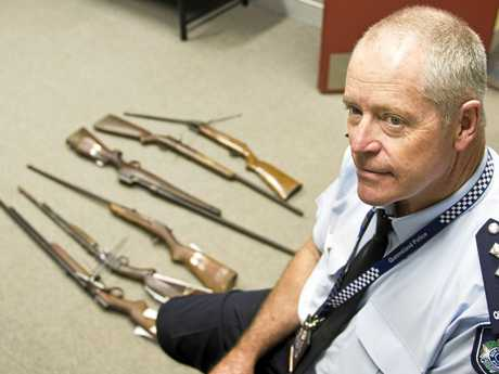 GUNS GATHERED: Toowoomba City Patrol Group Inspector Stephen Angus with some of the rifles handed in during the final days of the National Gun Amnesty.