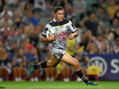 Te Maire Martin of the Cowboys runs with the ball to score a try