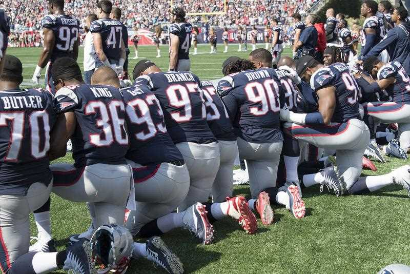 New England Patriots players hold hands and kneel during the National Anthem prior to the start of their game against the Houston Texans at Gillette Stadium in Foxboro, Massachusetts, USA, 24 September 2017.