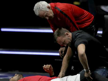 John McEnroe (top) looks on as Nick Kyrgios receives treatment at the Laver Cup.