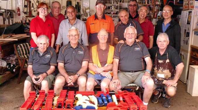 Arncliffe Men's Shed members proudly presenting the wooden toys made for children in local hospitals.