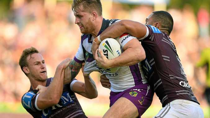 Cameron Munster of the Storm is tackled by Daly Cherry-Evans, (left), and Dylan Walker of the Sea Eagles