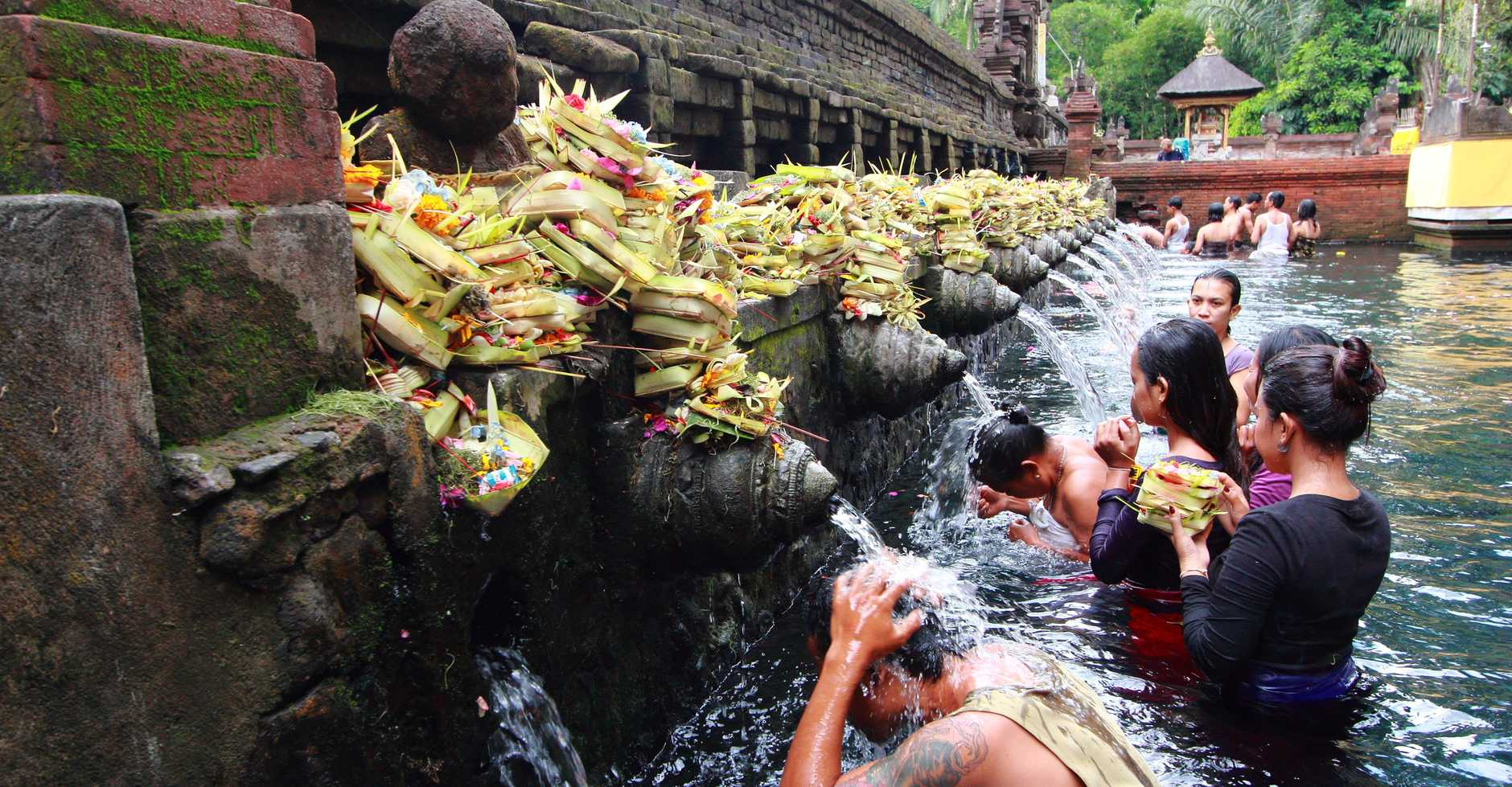 Worshippers make an offering at the Tirta Empul Temple in Bali and, below, the The Wyndham Jivva Resort reception.