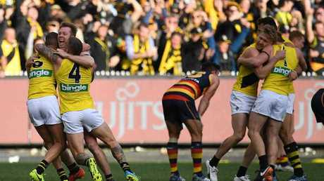 (L-R) Shaun Grigg, Jack Riewoldt and Dustin Martin reacts after winning the AFL grand final between the Adelaide Crows and Richmond Tigers at the MCG in Melbourne, Saturday, September 30, 2017.