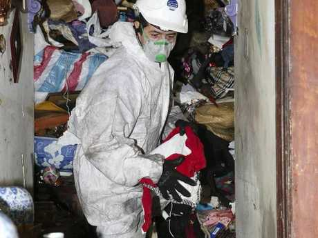 One of Cook's workmen ploughs through the rubbish inside 43 Waterloo Street.Source:News Corp Australia