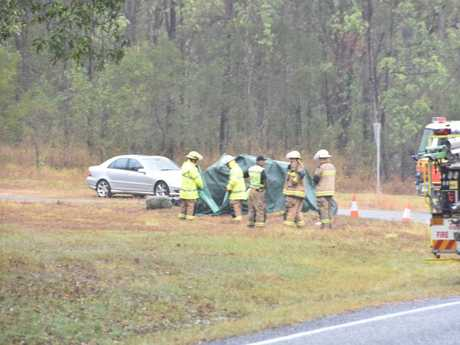 TRAGEDY: Emergency services personnel covered the Kia with a green tarp after the fatal crash.