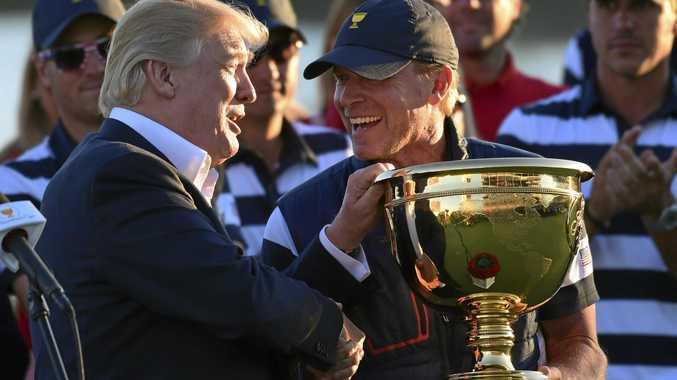 President Donald Trump, left, presents the winner's trophy to US team captain Steve Stricker.