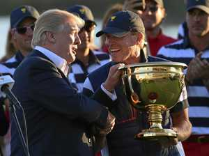 President Donald Trump, left, presents the winner's trophy to US team captain Steve Stricker.