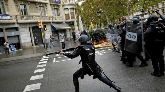 A Spanish riot police officer shoots a rubber bullet at people trying to reach a voting site at a school in Barcelona.