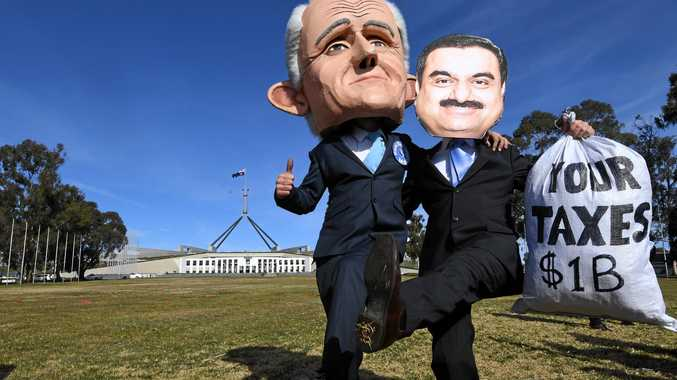 Protesters wearing masks of Australian Prime Minister Malcolm Turnbull and Adani chairman Gautam Adani make a point during a rally against the Adani mine, outside Parliament House in Canberra recently.