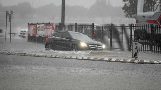 A Mercedes tries to get through flooded water in Bundaberg.