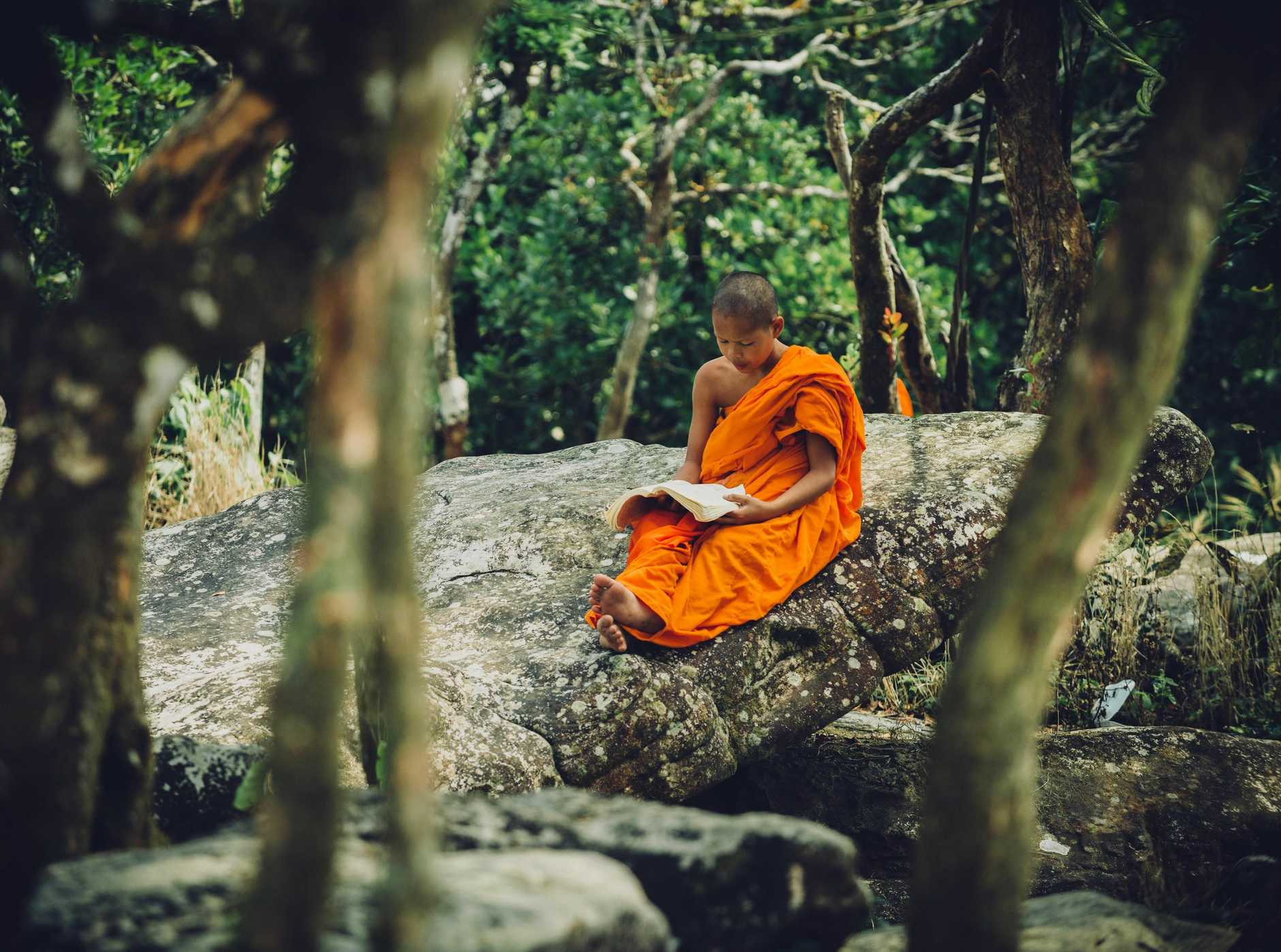 CALM CORNER: A Cambodian Buddhist reads a book under a tree near a temple on a hill in Bokor National Park in Cambodia.