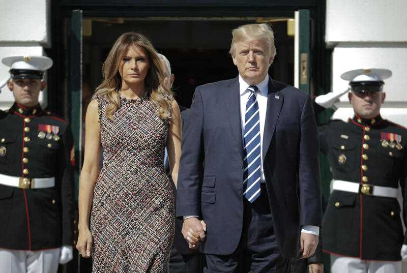 President Donald Trump and first lady Melania Trump holds hands as they arrive to observe a moment of silence to remember the victims of the mass shooting in Las Vegas
