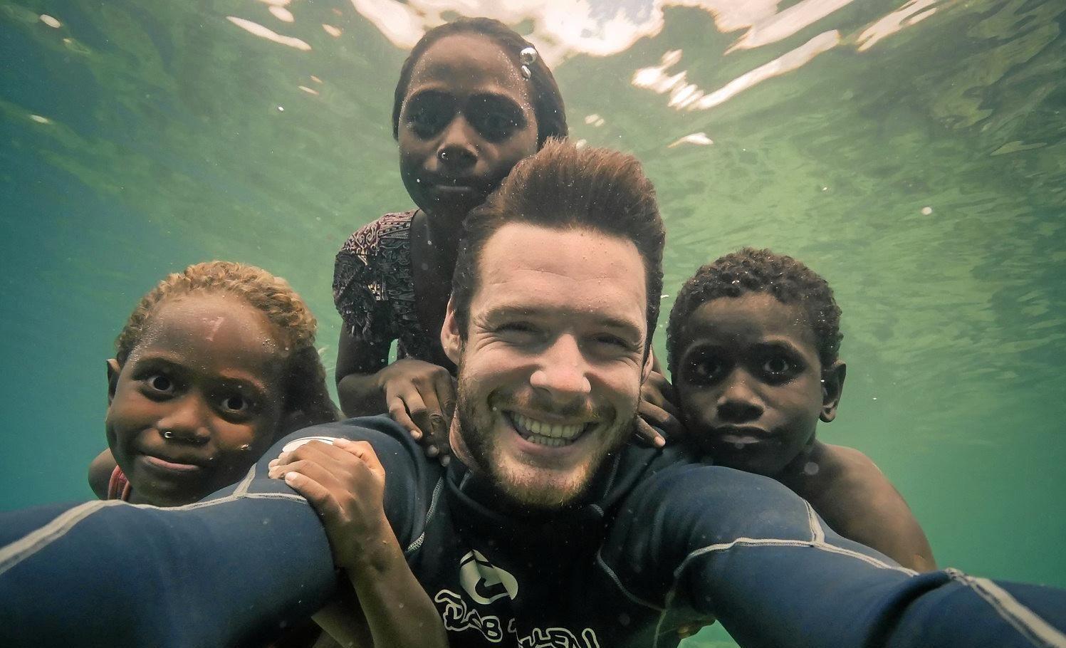 Marine biologist Lucas Handley takes an underwater selfie with children in the Solomon Islands. He stars in the movie Blue.