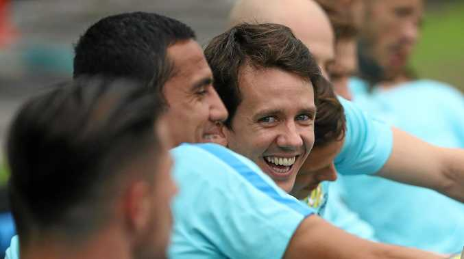 ALL SMILES: Robbie Kruse stretches during a Socceroos training session.