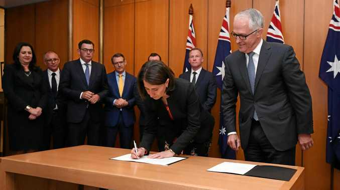 Australian Prime Minister Malcolm Turnbull and state leaders look on as NSW Premier Gladys Berejiklian signs an agreement at a special meeting on counter-terrorism of the Council of Australian Governments, at Parliament House, Canberra.