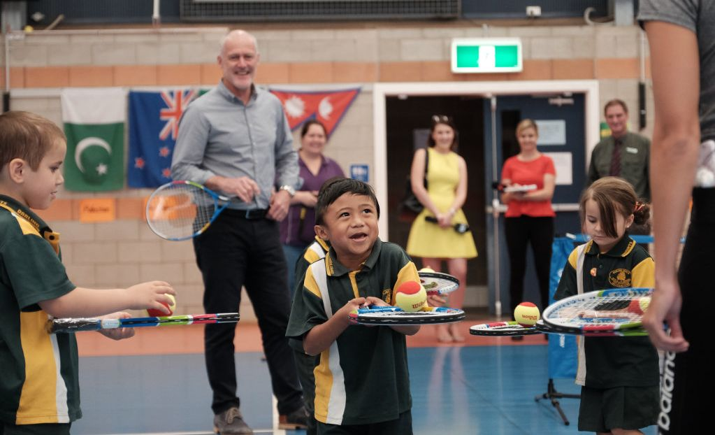 Darling Heights State School prep student Kiel Rodriguez is excited to get his hands on a new tennis racquet, as Australian tennis great John Fitzgerald (behind) watches on.