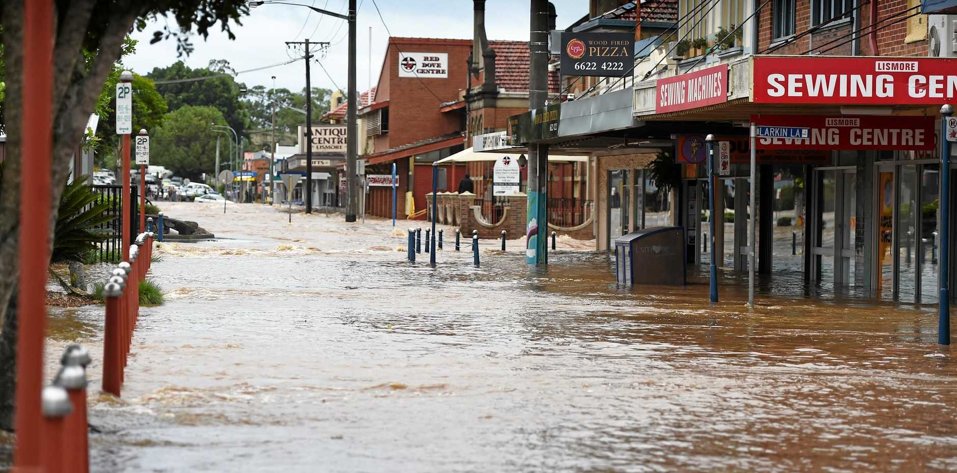 Heavy flood water tearing through the Lismore CBD in April this year.