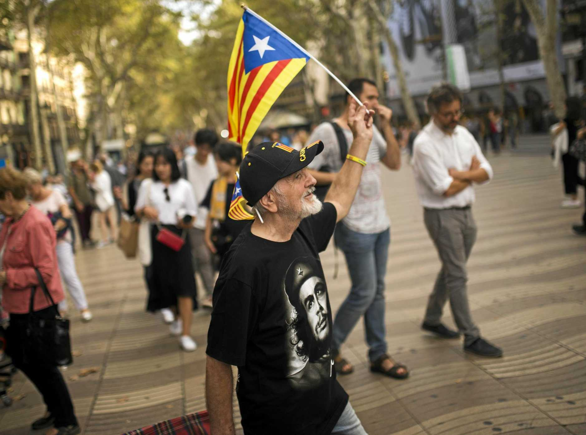 A Barcelona resident waves the Catalonia independence flag as he walks along the Ramblas in Barcelona.