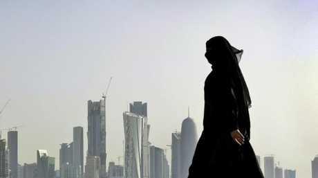 A Qatari woman walks in front of the city skyline in Doha, Qatar. Picture: Kamran Jebreili/APSource:AAP