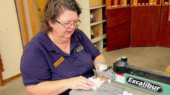 Cheryl Whitechurch working on a wooden jigsaw piece .