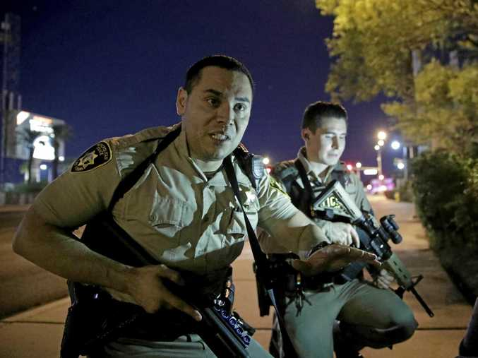 Police officers advise people to take cover near the scene of a shooting near the Mandalay Bay resort and casino on the Las Vegas Strip, on Sunday, October 1. (AP Photo/John Locher)