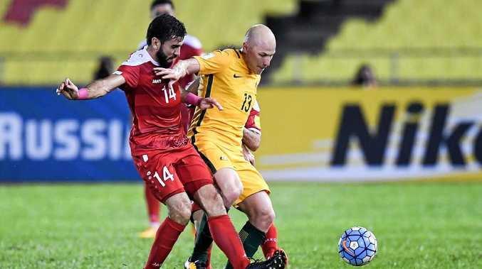 MIDFIELD BATTLE: Australia's Aaron Mooy and Syria's Tamer Hag Mohamad in the first leg.