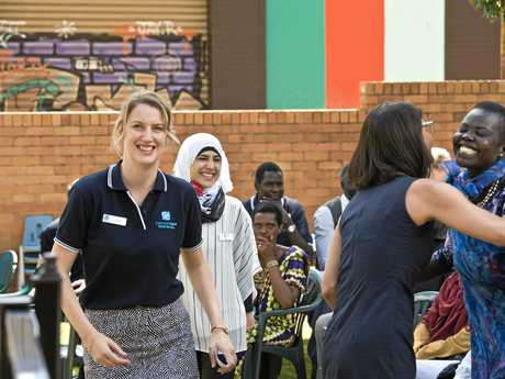 TRAMS co-ordinator Hannah Belesky (left) and Zahra Hashimi walk past as Catholic Care director Kate Venables and Aguil De'Chutdeng (right) embrace as Toowoomba Refugee and Migrant Support moves into a new home in Ruthven St.