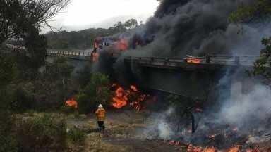 B-Double engulfed in flames on bridge edge.