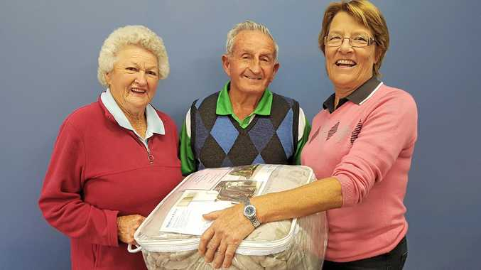 FIRST: Marge and Ken Burley are presented with the Lane Cup prize by Marg Adcock after their fourth successive cup win at the Warwick Golf Club.