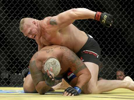Brock Lesnar batters Mark Hunt during their heavyweight mixed martial arts bout at UFC 200,  in Las Vegas.