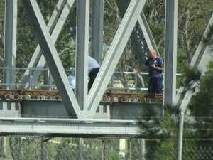 Emergency services called as man climbs train bridge
