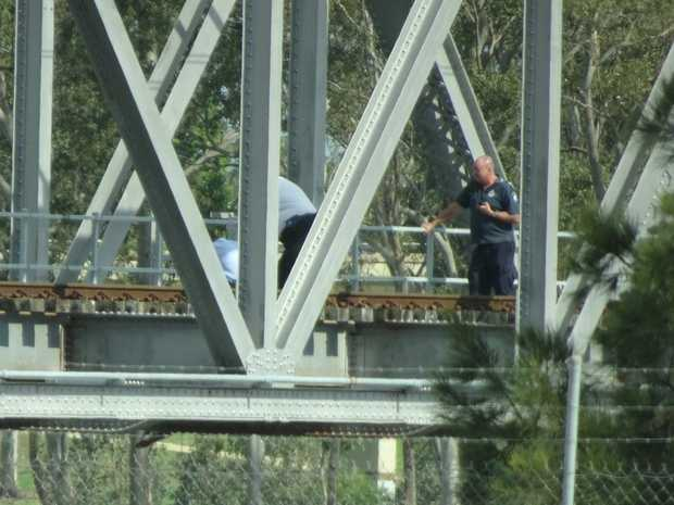 MAN CLIMBS BRIDGE: A witness was able to capture a photo of the drama that unfolded on the rail bridge across the Burnett River this morning.