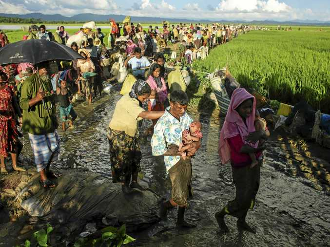 Hundreds of Rohingya wait after crossing Bangladesh's border as they flee from Budichong, Myanmar after crossing the Naf river.
