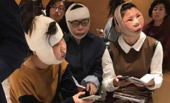 SURGERY PROBLEMS: The women — wrapped chin-to-dome in bandages — were barred from boarding a flight home at an airport in South Korea.
