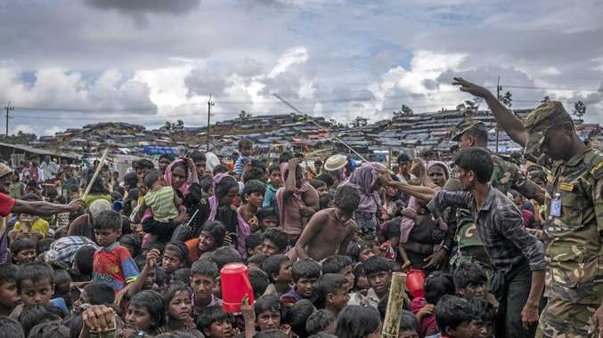 Police stand guard at a refugee camp in Cox's Bazar, Bangladesh, where Rohingya refugees from Myanmar have fled.